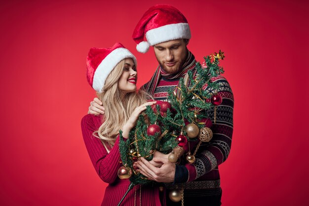 Mann und frau weihnachtsbaum spielzeug spaß urlaub roten hintergrund
