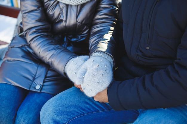 Mann und frau winter kalter frost umarmt hände in warmen handschuhen