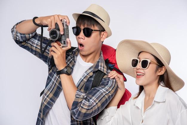 Mann und frau zogen sich an, um zu reisen, eine brille zu tragen und fotos zu machen