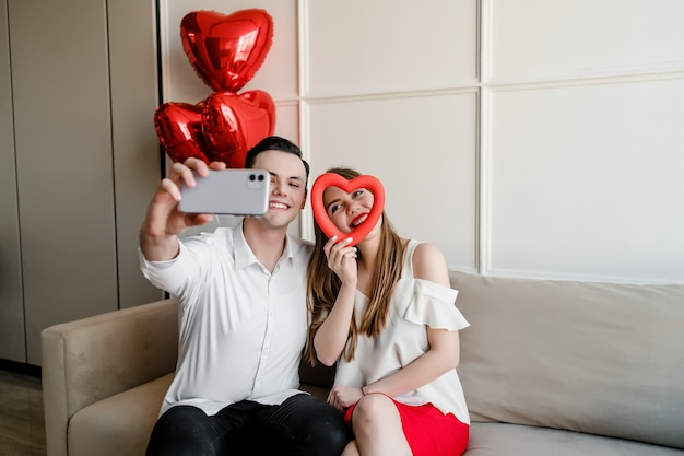 Mann und frau zu hause, die selfie mit herzen und ballonen am telefon machen