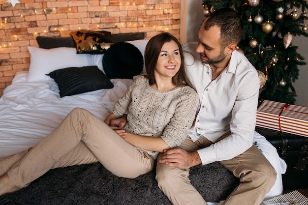 Mann und frau zu hause nahe weihnachtsbaum. paar verliebt auf dem bett