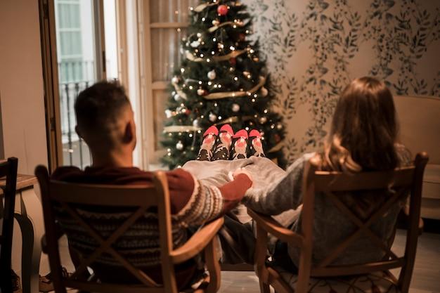 Mann- und frauenhändchenhalten auf stühlen nähern sich weihnachtsbaum