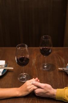 Mann- und frauenhändchenhalten bei tisch mit gläsern wein im restaurant