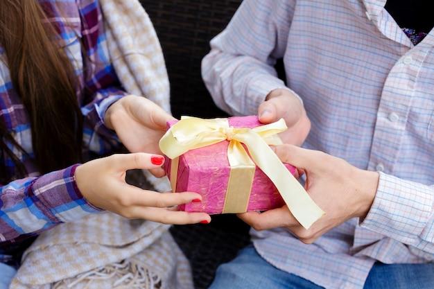 Mann- und frauenhände, die eine rosa geschenkbox halten.