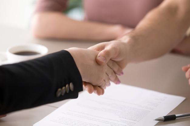 Mann- und frauenhändeschütteln nach dem unterzeichnen von dokumenten, erfolgreiches abkommen, nahaufnahme