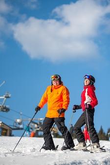 Mann- und frauenskifahrer mit skis am winterurlaubsort
