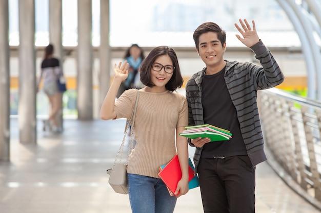 Mann- und frauenstudenten, die viele bücher halten, die hände wellenartig bewegen, sagen ihren freunden hallo
