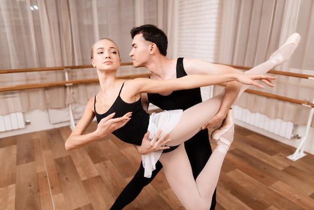 Mann- und frauentänzer, die in der ballettklasse aufwerfen.