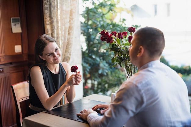 Mann und freundliche junge frau mit der blume, die am tisch sitzt