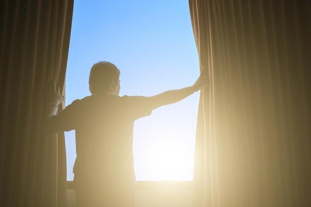 Mann und hoffnung konzept. mann, der fenstervorhänge öffnet