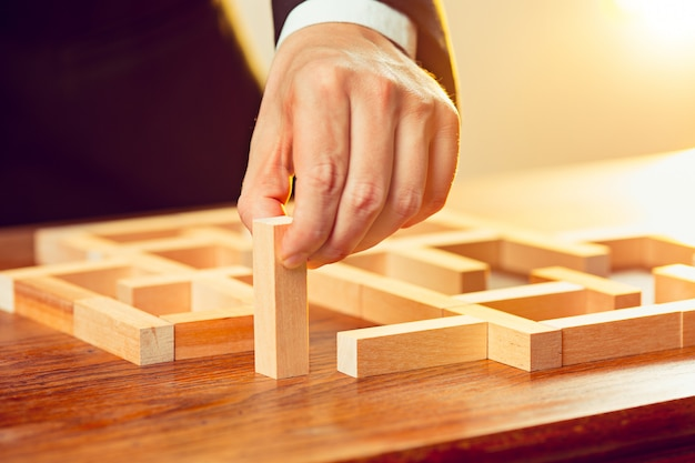 Mann und holzwürfel auf tisch. managementkonzept