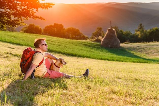 Mann und hund, die auf einer bergwiese sitzen und sonnenuntergang genießen