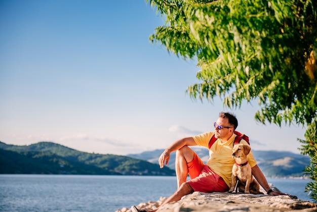 Mann und hund sitzen auf einem steinernen dock am meer