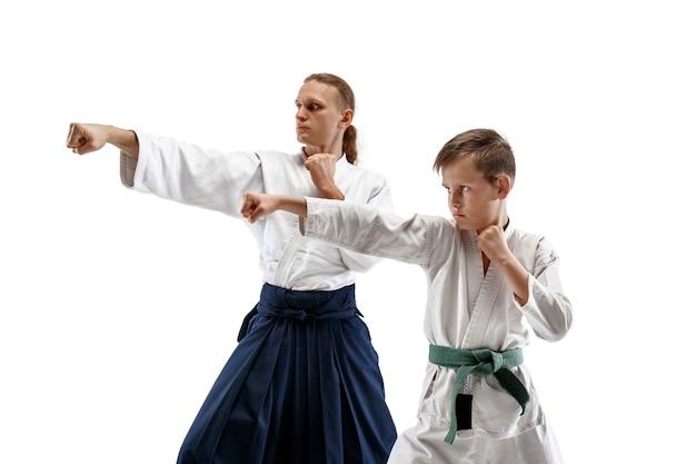 Mann und jugendlicher junge kämpfen am aikido-training in der kampfkunstschule. gesunder lebensstil und sportkonzept. kämpfer im weißen kimono auf weißer wand. karate-männer mit konzentrierten gesichtern in uniform.