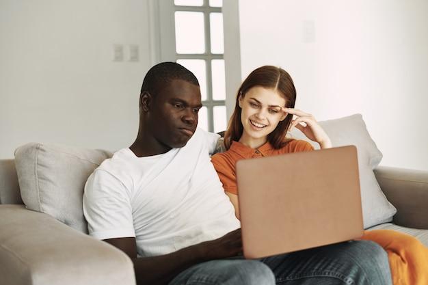Mann und junge frau mit laptop auf schoß internetfreunde kommunikation interieur