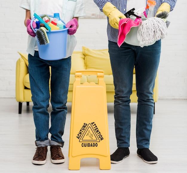 Mann und junge halten eimer mit produkten vor nassem bodenschild