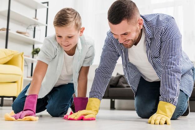 Mann und junge putzen den boden