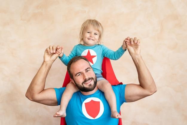 Mann und kind superheld zu hause. superheld vater und sohn haben spaß zusammen.