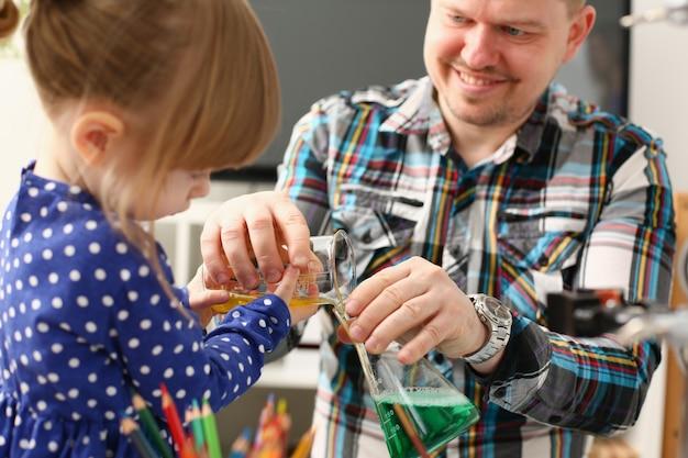Mann und kleines mädchen spielen mit bunten flüssigkeiten