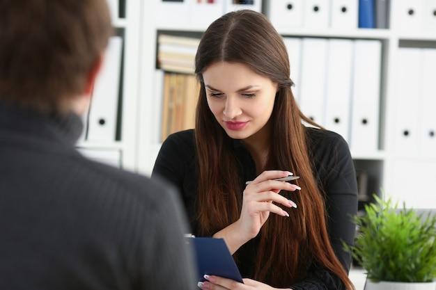 Mann und lächelnde reife frau sprechen im büro