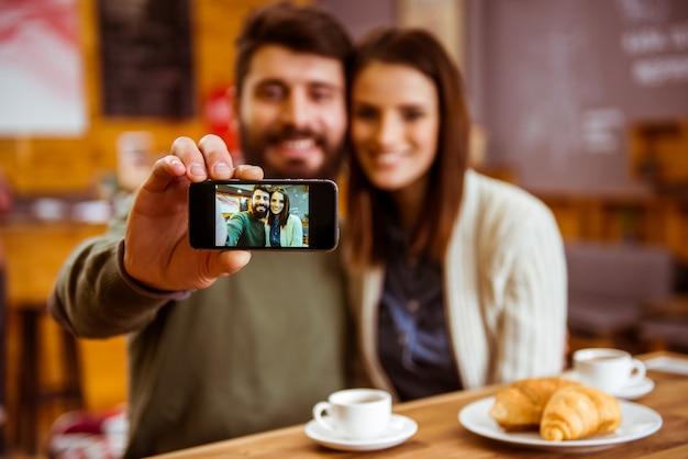Mann und mädchen, die selfie stelle und das lächeln machen.