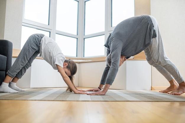 Mann und mädchen in hauskleidung beim yoga