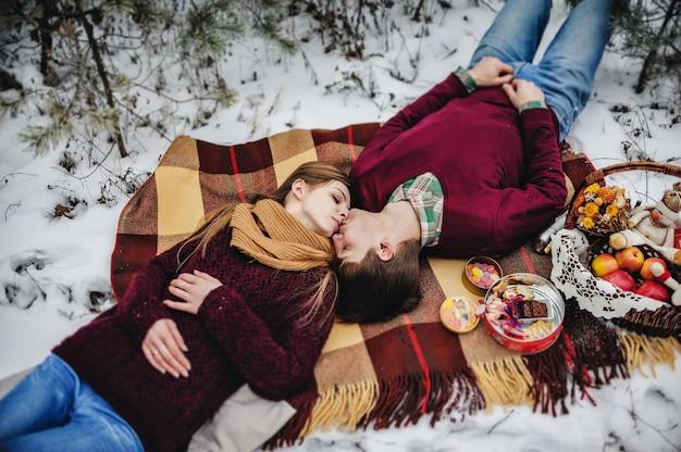 Mann und mädchen legen sich beim winterpicknick am valentinstag in einem verschneiten park auf eine decke. weihnachtsferien, feier. draufsicht, flach liegen.