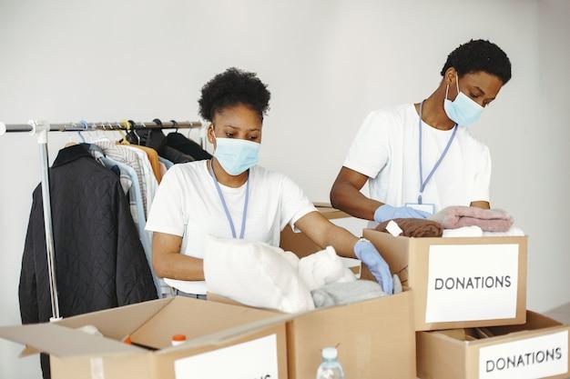 Mann und mädchen mit kontrollkästchen. afrikanische freiwillige in masken. boxen mit humanitärer hilfe.