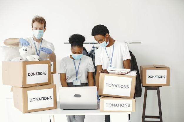 Mann und mädchen mit kontrollkästchen freiwillige in masken mit laptop-boxen mit humanitärer hilfe