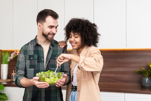 Mann und schöne frau, die geschmackvollen salat versuchen