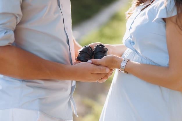 Mann und schwangere frau halten schuhe für neugeborenes baby in ihren armen, die auf dem grünen feld stehen