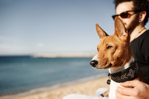 Mann und sein hund am strand bewundern das meer
