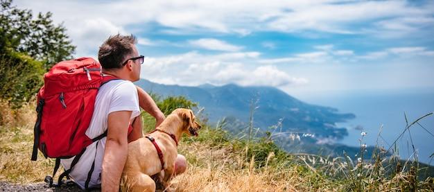 Mann und sein hund, die auf berg sitzen und meer betrachten
