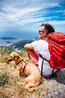 Mann und sein hund, die auf dem boden sitzen und meer betrachten