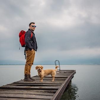 Mann und sein hund, die auf hölzernem dock stehen