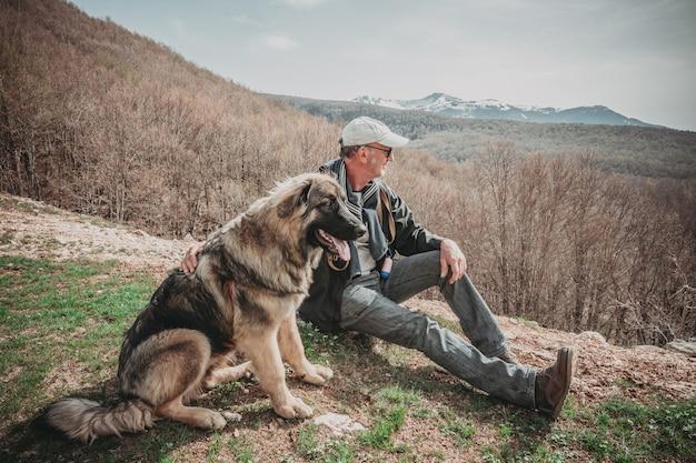 Mann und sein hund, die die berge schauend sitzen