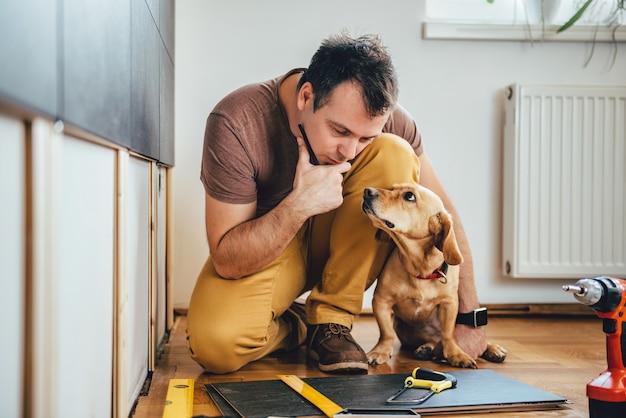 Mann und sein hund, die zu hause erneuerungsarbeiten erledigen