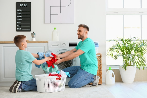 Mann und sein kleiner sohn machen zu hause wäsche