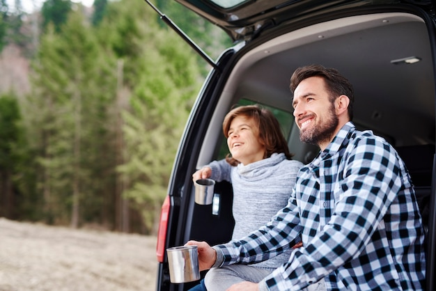 Mann und sein sohn genießen die aussicht während des roadtrips