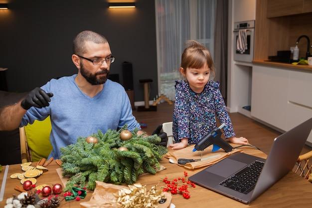 Mann und seine kleine tochter lernen, einen weihnachtskranz online zu dekorieren