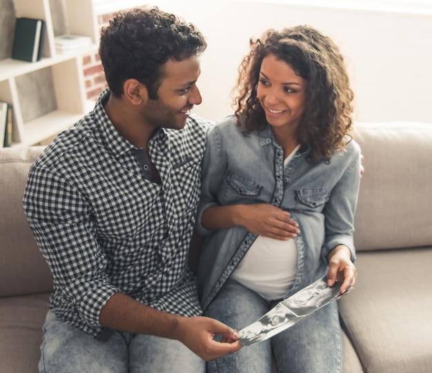Mann und seine schöne schwangere frau passen sonogramm auf