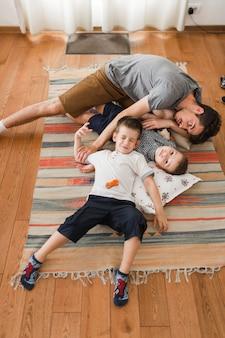 Mann und seine zwei söhne, die auf wolldecke sich entspannen