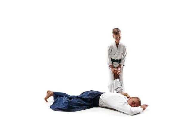 Mann und teenager kämpfen beim aikido-training in der kampfkunstschule. gesunder lebensstil und sportkonzept. kämpfer im weißen kimono an der weißen wand. karate-männer mit konzentrierten gesichtern in uniform.