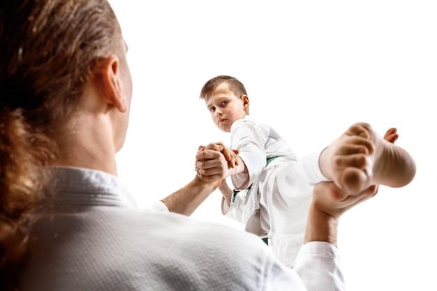 Mann und teenager kämpfen beim aikido-training in der kampfkunstschule. gesunder lebensstil und sportkonzept. kämpfer im weißen kimono auf weißem hintergrund. karate-männer mit konzentrierten gesichtern in uniform.