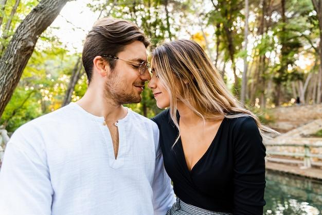 Mann und verliebte frau in einem park, der einen romantischen kuss hat.