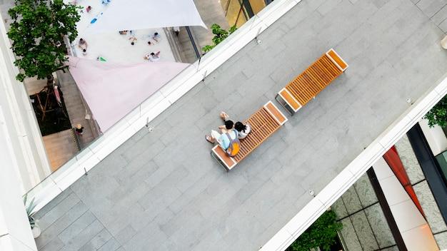 Mann und verliebte frau sitzen auf holzbank am fußgängerweg in der oberen luftaufnahme