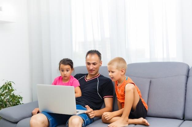 Mann und zwei kinder, die beim wohnzimmerlächeln sitzen