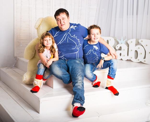 Mann und zwei kinder sitzen lächelnd im wohnzimmer.