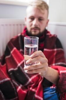 Mann unter Decke mit Glas Wasser