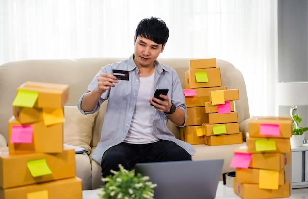Mann unternehmer, der ein smartphone mit kreditkarte im heimbüro verwendet